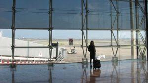 vrouw op vliegveld met koffer